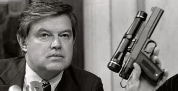"""Spy Guns: Senator Frank Church holding the """"Heart Attack Gun"""" during a 1975 Senate hearing, which detailed the existence of the weapon (Public Domain)."""