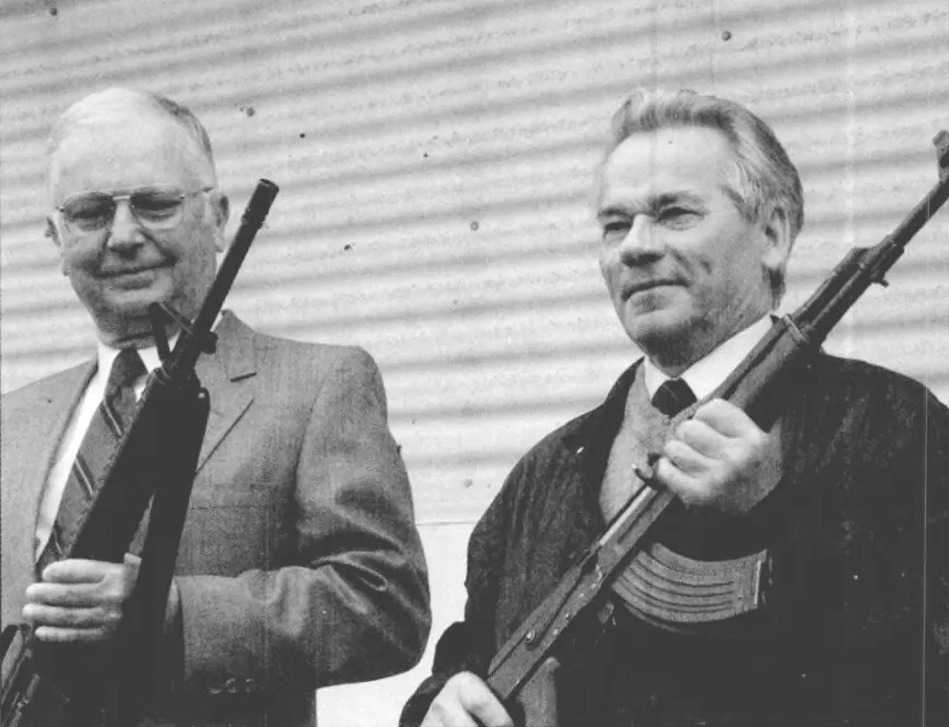 Eugene M. Stoner, left, and Mikhail T. Kalashnikov hold the rifles they designed, taken May 1990. (Photo by Sgt. Chris Lawson/Public Domain).
