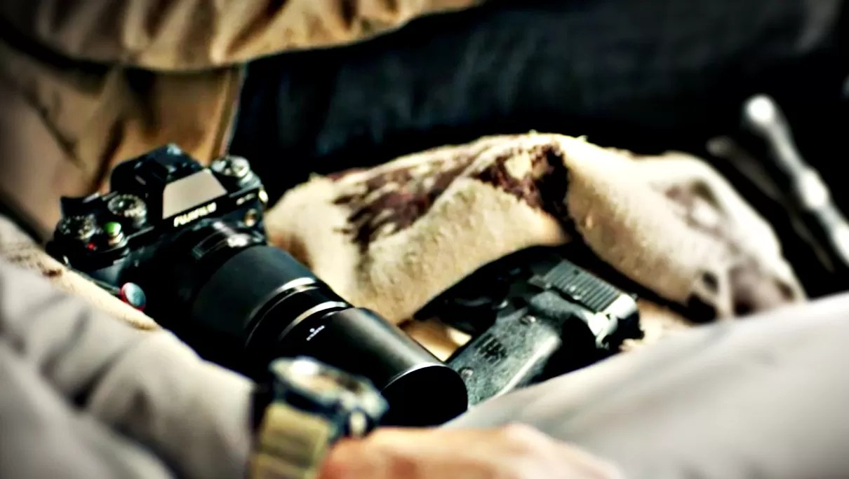 Surveillance from a car. Camera with a telephoto lens, handgun at the ready, and a cover cloth to conceal both.