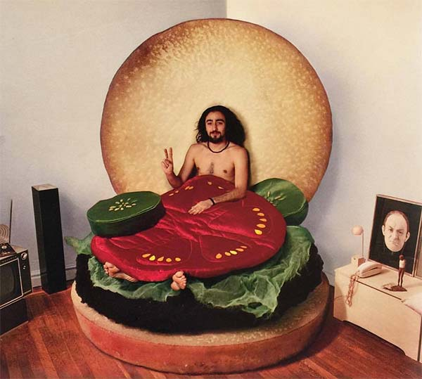 men sitting in a burger shaped bed