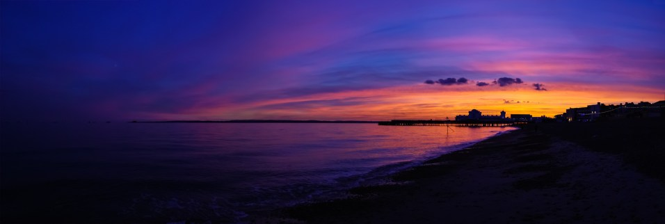 A panoramic view of a golden sunset showing a silhouette of South Parade Pier, the beach, sea and Isle of Wight. Southsea, UK