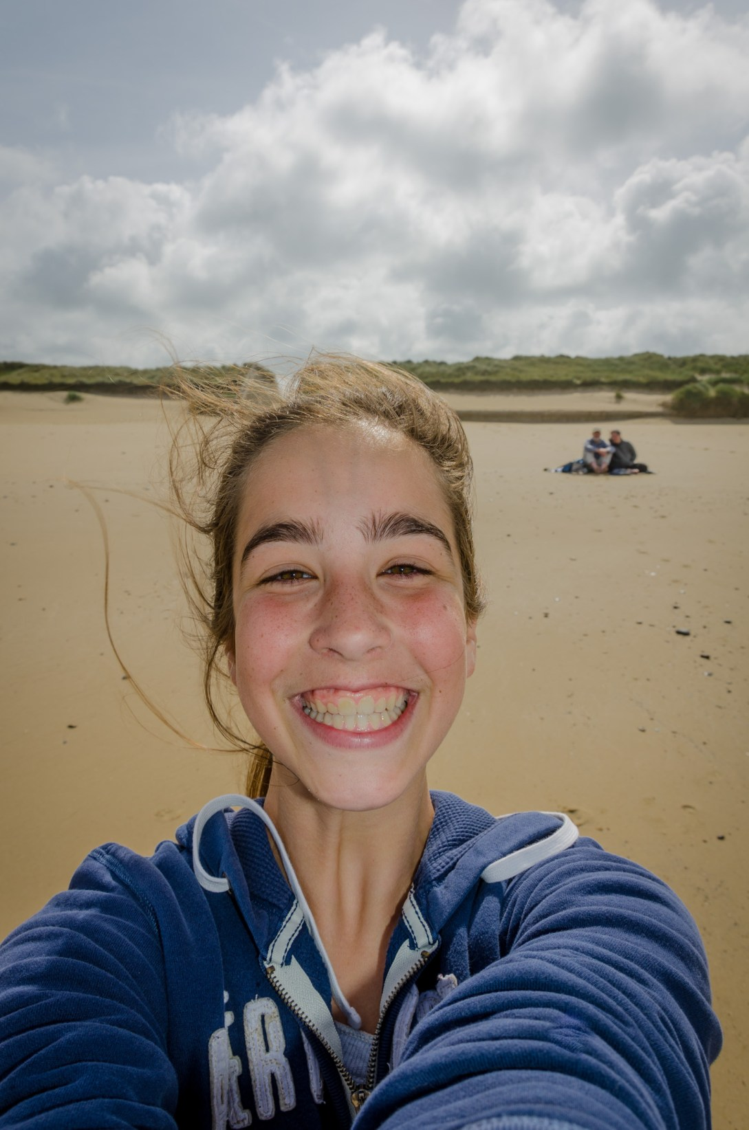 Selfie - Lanie on the beach with Ginger and Gary in background