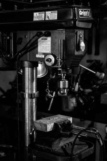 A black and white photograph of a Grizzly drill press