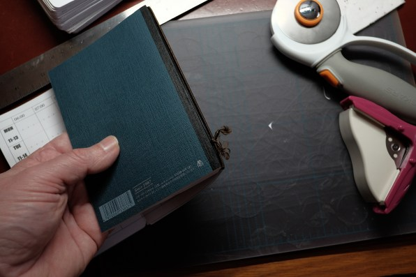The shock cord is knotted at the back to make a loop, and it's held around the spine of the notebook.