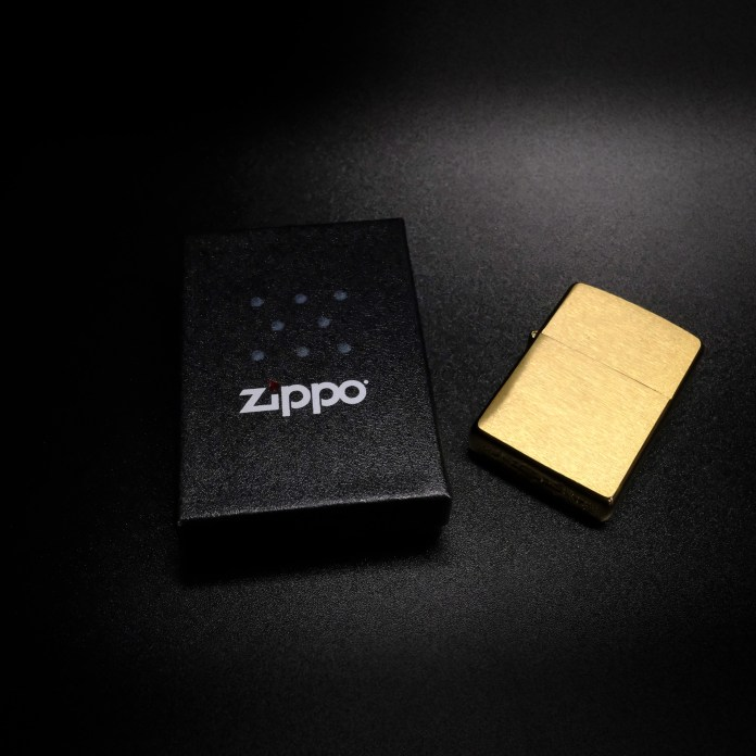 Photograph of a brass Zippo lighter with packaging