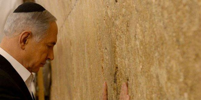 Israeli Prime Minister Benjamin Netanyahu prays at the Western Wall before his departure to the US to address Congress. (Photo: GPO)