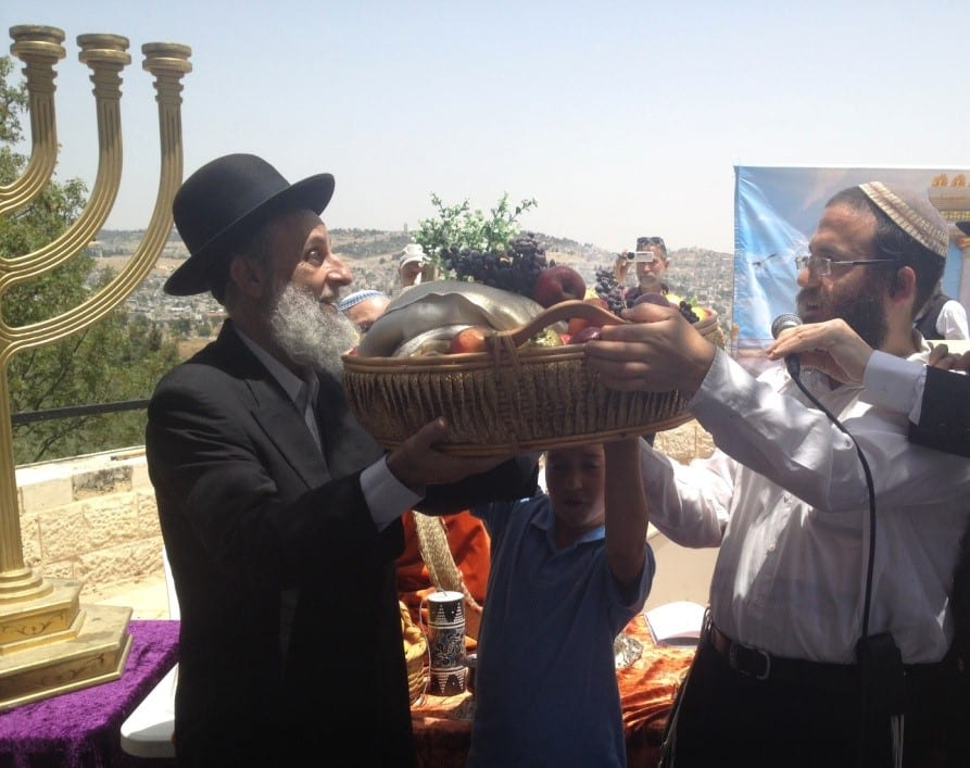 A Levite (right), whose family served in the Temple, brings the basket of First Fruits and hands it to the Cohen (left). (Photo: Yisrael Rosenberg/ Breaking Israel News)