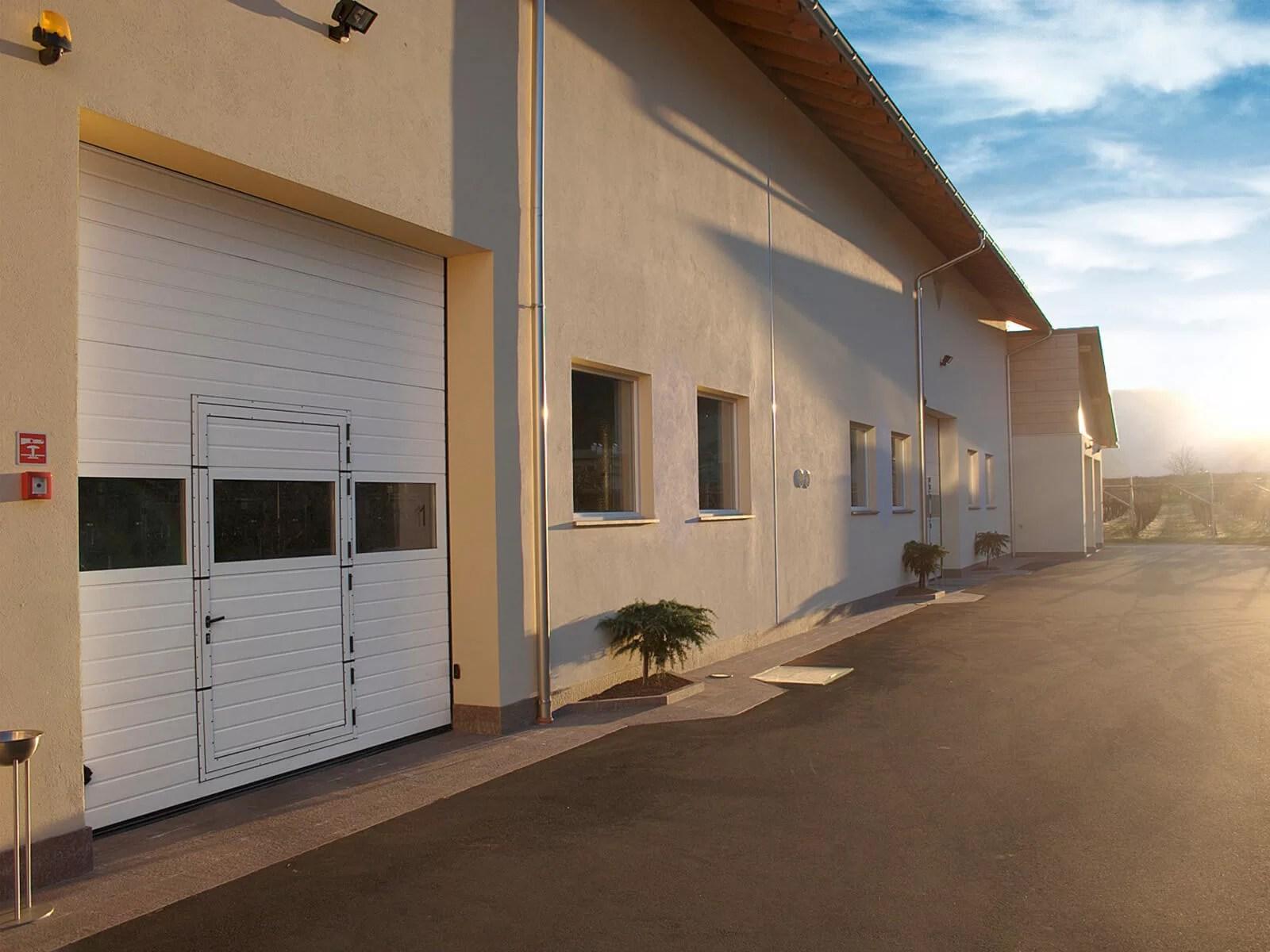Portone sezionale industriale SECURA - Stucco bianco C21 Visa porta pedonale