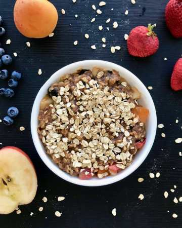 Vegan fruit dessert in a bowl surrounded by fruit.