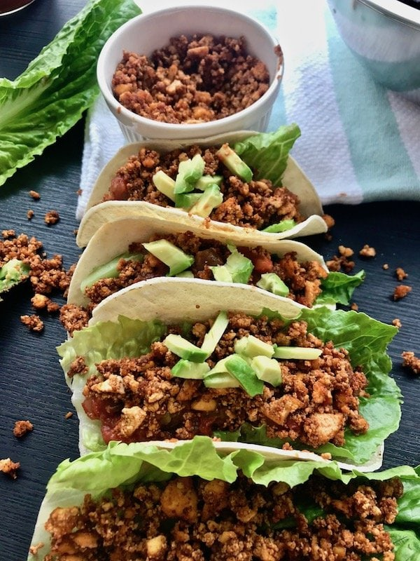 Vegan tacos filled with tofu crumble, lettuce, salsa, and avocado.