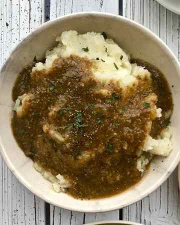 Mushroom gravy on a bowl of mashed potatoes.