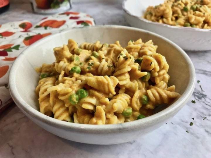 Close-up of bowl of vegan pumpkin pasta with peas.