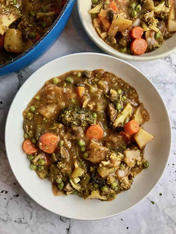 Two bowls of vegetable stew with broccoli, potato, carrot, peas.