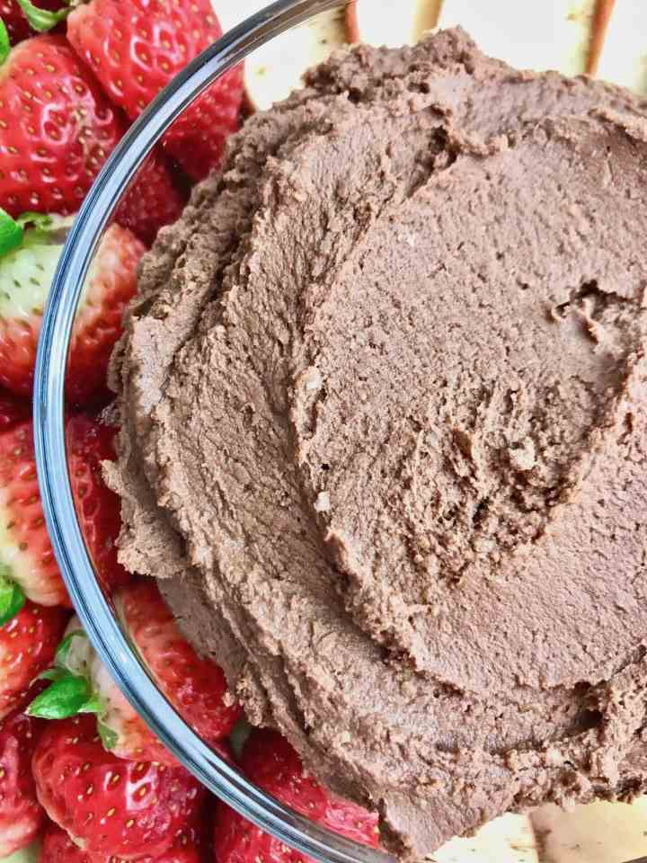 Close up of half a bowl of dessert hummus with strawberries next to it.