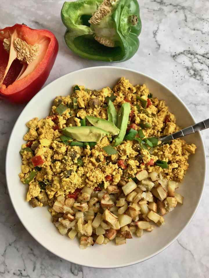 Tofu scramble with a side of potatoes, topped with avocado. A green and red pepper are on the table next to the bowl.