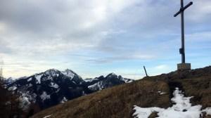 Hinter dem Gipfelkreuz erhebt sich der Wendelstein