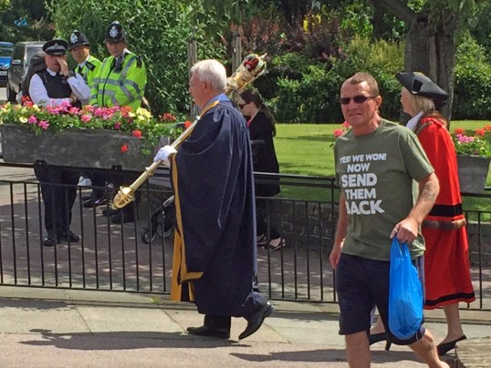 In this photo made available by Diamond Geezer, a man wearing an anti immigration T-shirt walks during Armed Forces Day Parade in Romford, England, Saturday 25 June 2016. Britain's Prime Minister David Cameron and the Mayor of London Sadiq Khan warned Monday June 27, 2016 that abuse directed at immigrants wouldn't be tolerated, after a series of incidents were reported following the country's decision to leave the European Union. ( Diamond Geezer via AP)