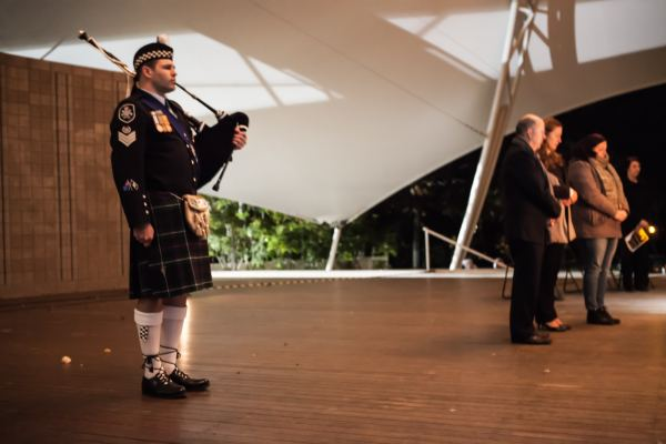 The bagpiper with the speakers standing for a minute's silence
