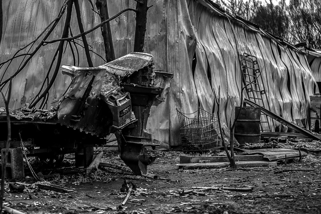 A burnt-out boat next to a shed on a property that was destroyed by the bushfires