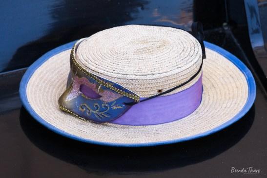 Gondolier hat and mask resting on seat of gondola.