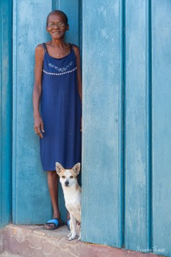 Cuba, Trinidad. A smiling woman stands in her blue doorway with her dog.