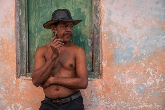 Man with cigar leaning against wall, Trinidad, Cuba.