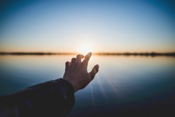 A hand reaching out for the sunset on the edge of the lake