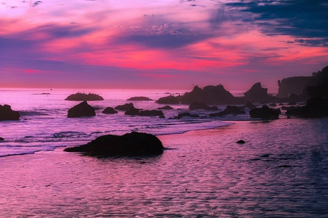A rocky ocean landscape beneath a purple and red sky