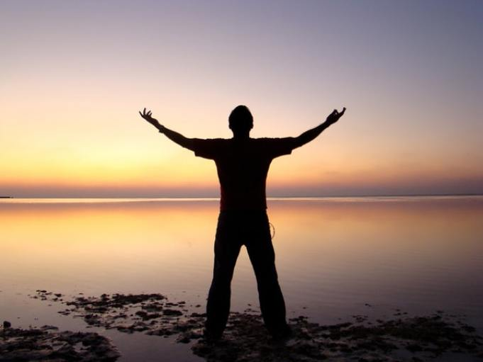 Silhouette of a man raising his arms to the sky at sunrise