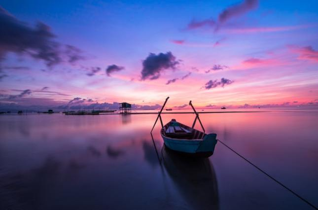 Abandoned boat in calm waters at sunset