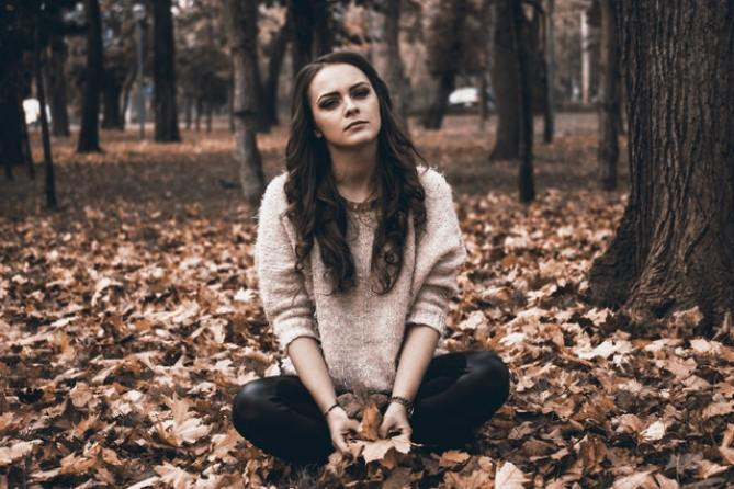Sad woman sitting in the forest