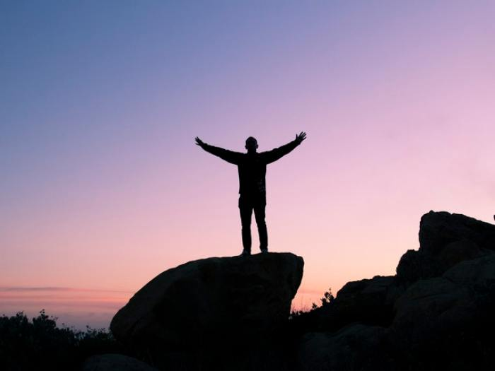 Man raising his arms in triumph on a boulder at sunset
