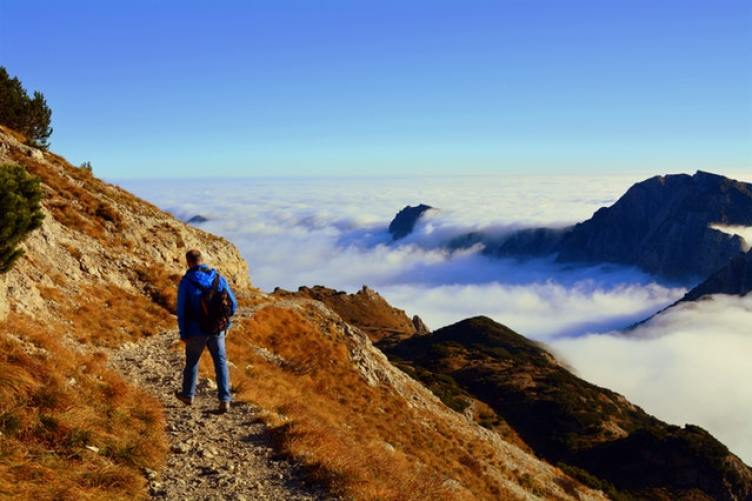 Man hiking on a cliff above the clouds