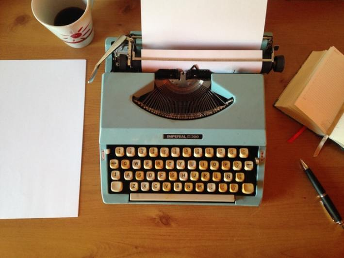 Typewriter on a desk with a blank sheet of paper