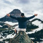 Man spreading his arms in triumph on the top of a mountain
