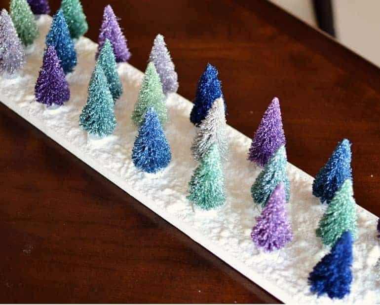 Turn some typical bottle brush trees, found at your local store, into this whimical Christmas scene with just a few crafty supplies!