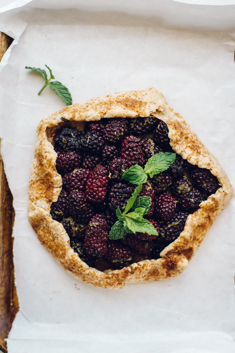 A blackberry mint galette on top of white parchment paper with fresh mint on top