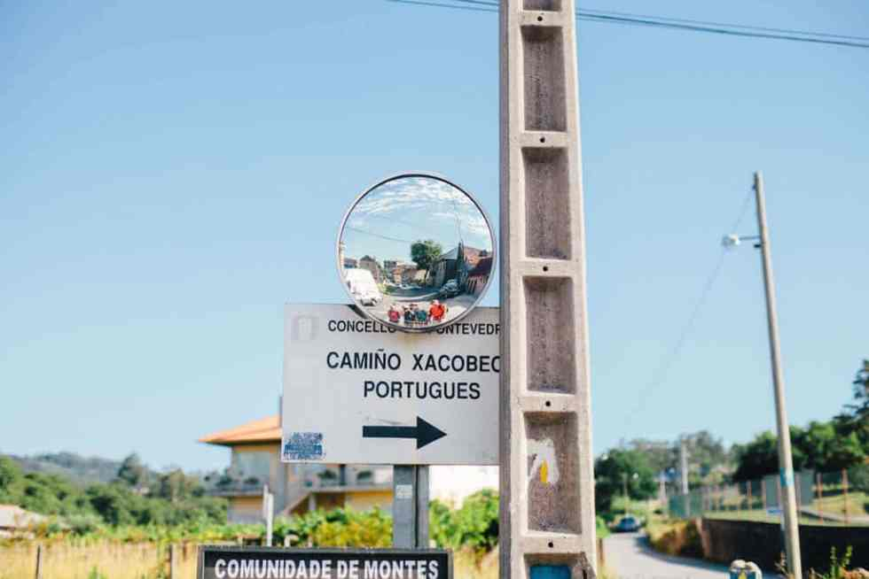 A reflector mirror and a sign pointing toward the Camino de Santiago