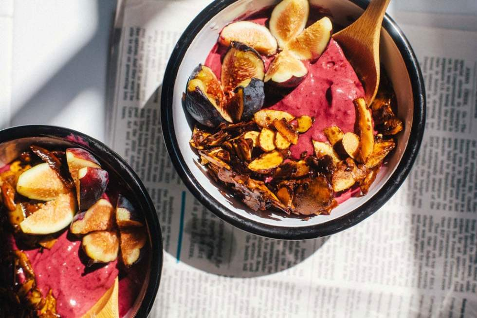 two acai frozen yogurt bowls in bright sunlight