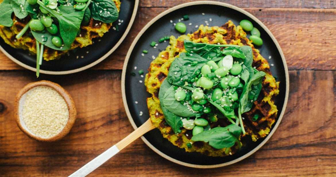 A stack of edamame falafel waffles topped with spinach, edamame, chives and sesame seeds.