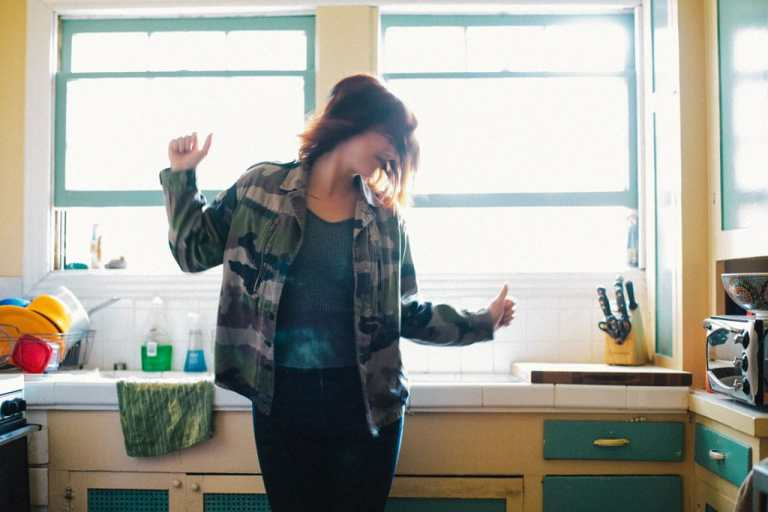 girl dancing in her kitchen in front of big, light filled windows.