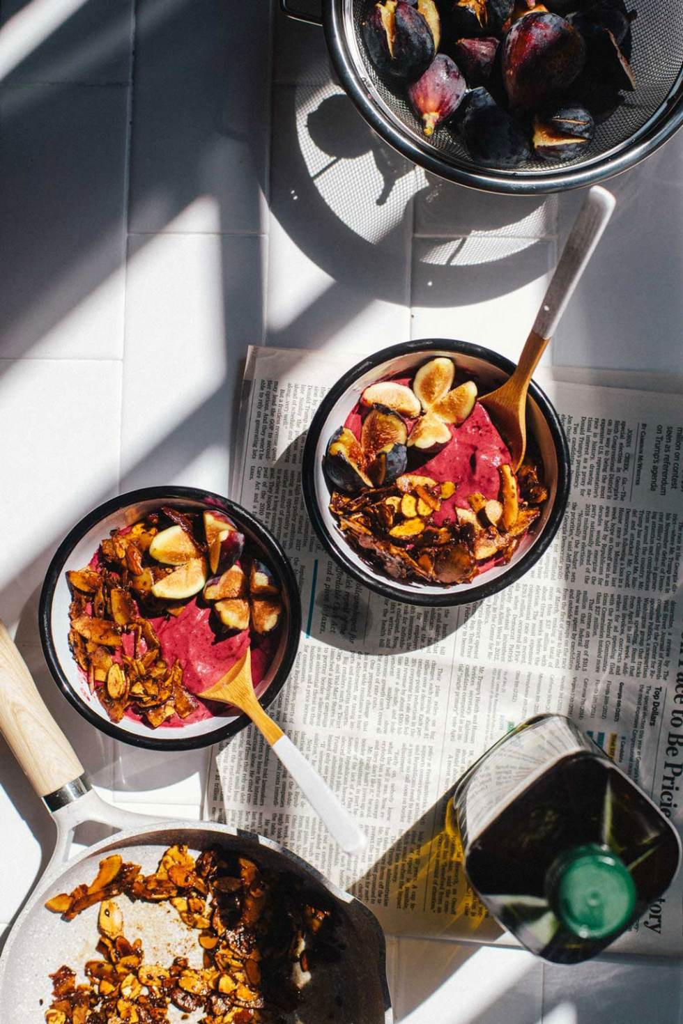 two bowls of blackberry acai frozen yogurt surrounded by a bowl of figs, a bottle of Pompeian olive oil and a skillet of olive oil granola crumble.