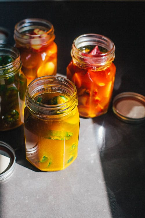 Four jars of pickles in a bright yellow sweet turmeric brine.