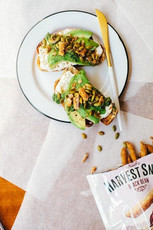 Avocado toast sprinkled with kale pesto, pepitas, and Harvest Snaps