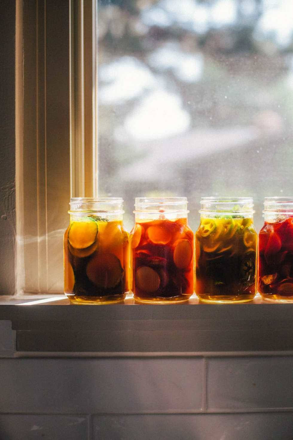 Four jars of pickles sitting on a window sill