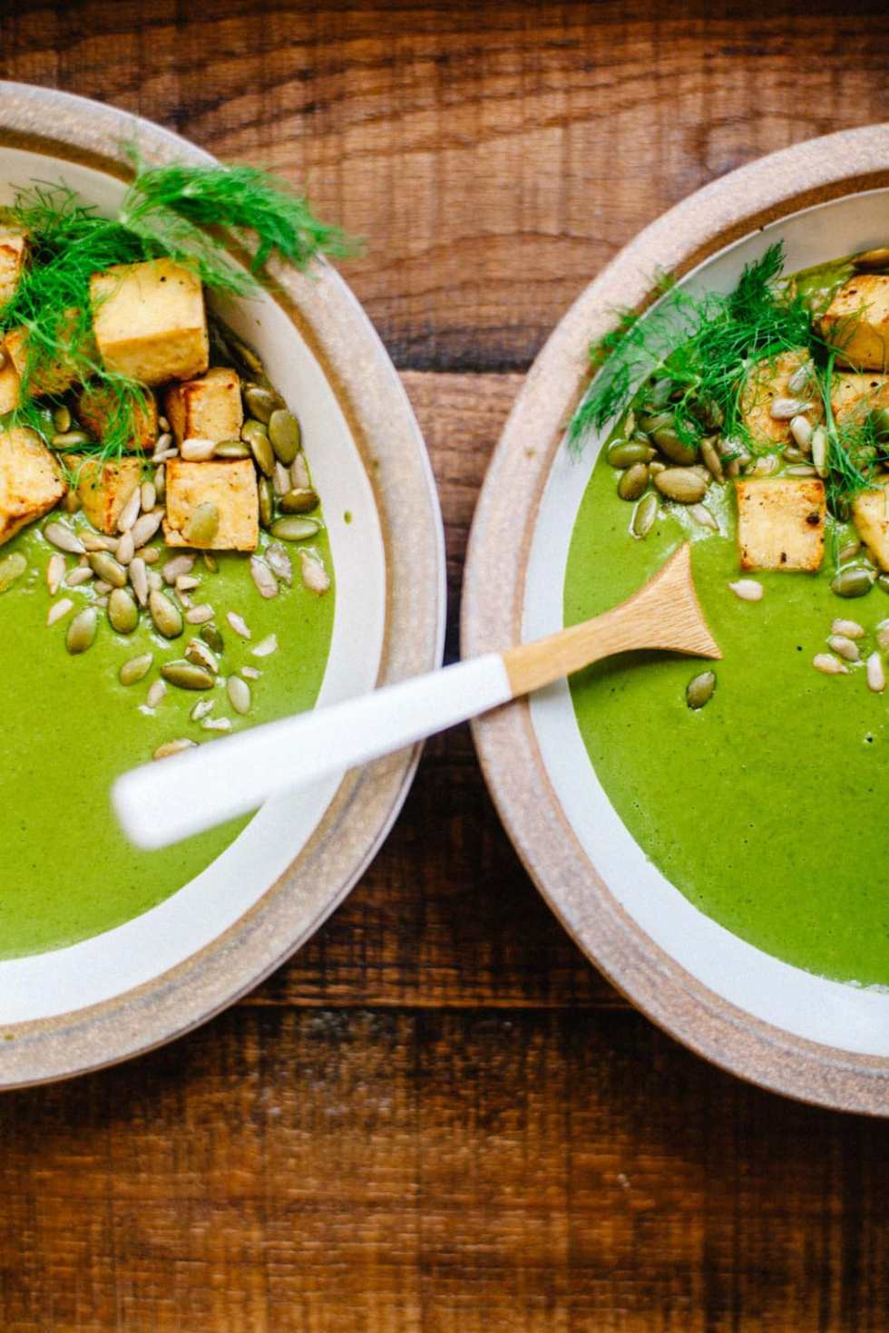 Two bowls of super green soup with fennel topped with tofu and seeds.