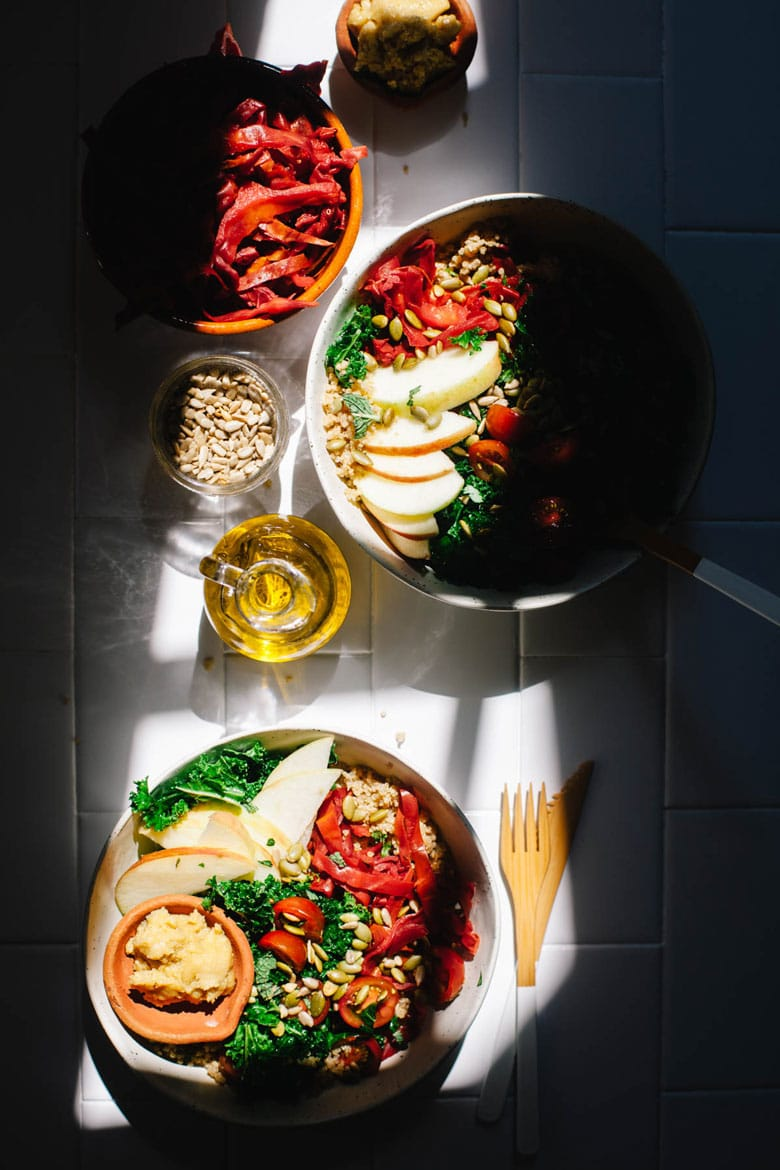 Two kale and quinoa bowls in a sliver of light