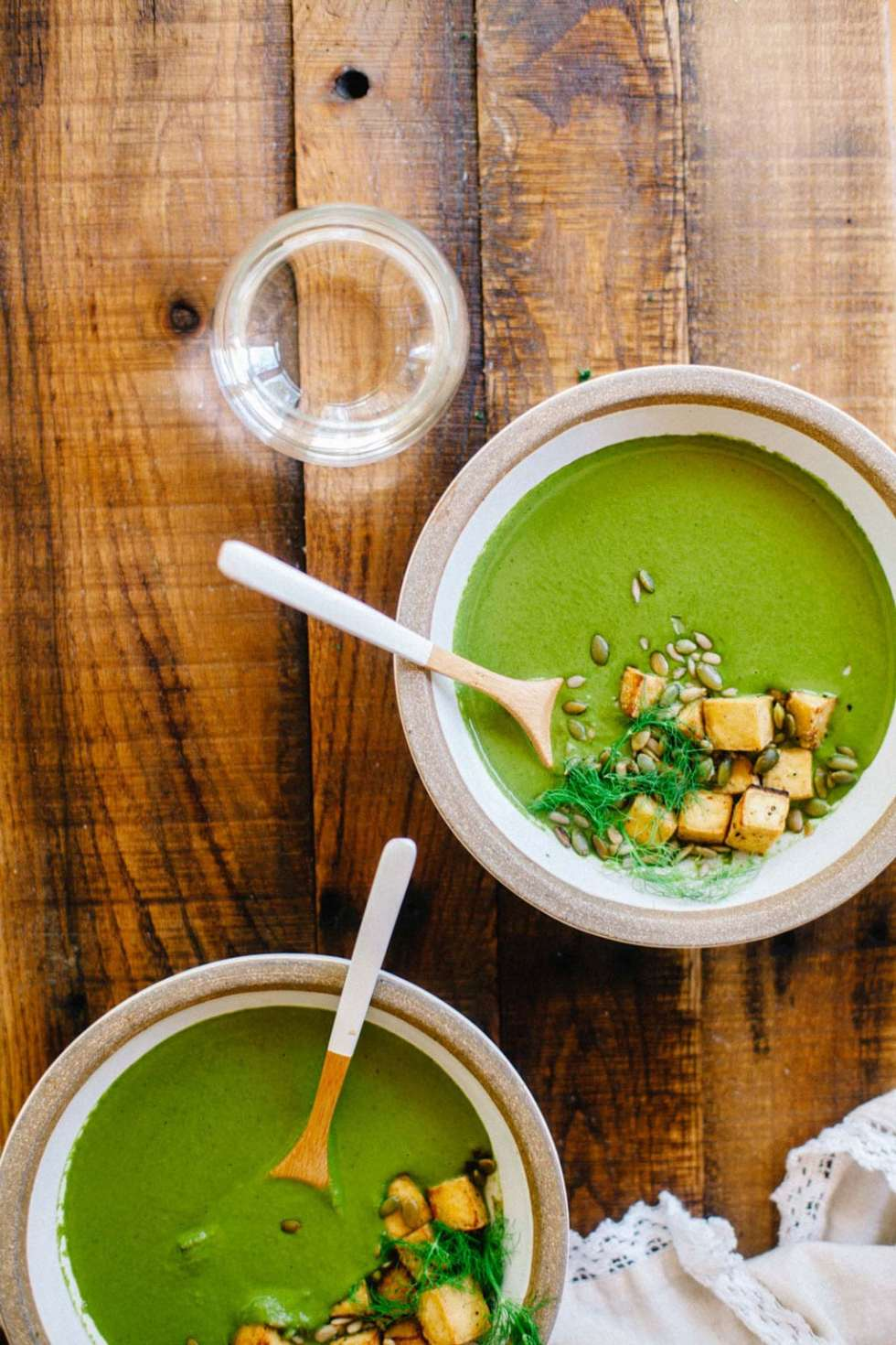 Two bowls of greens soup with crispy tofu on top.