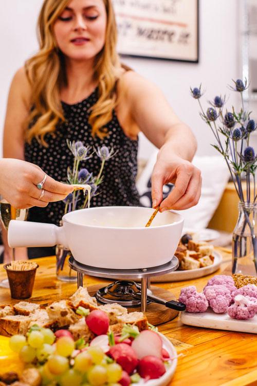 girl dipping cracker into fondue pot