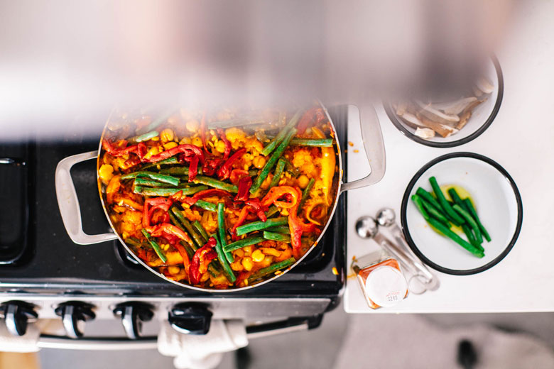 veggie paella cooking on a stove